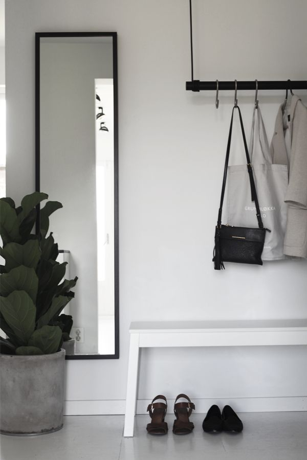 Minimalist nordic space saving entryway hallway with fiddle leaf fig plant and black framed mirror