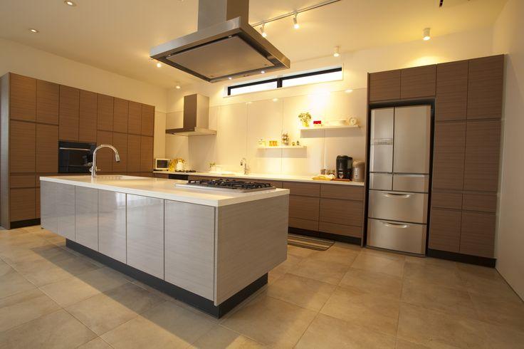 Elegancka, minimalistyczna aranżacja. Drewniane, brązowe szafki kuchenne. Jasna wyspa kuchenna    Elegant, minimalist interior. Wooden brown kitchen cabinets with a bright kitchen island