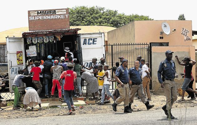 The security officers matching off the scene as the shop is looted.  xenophobia south africa 2015 - Google Search