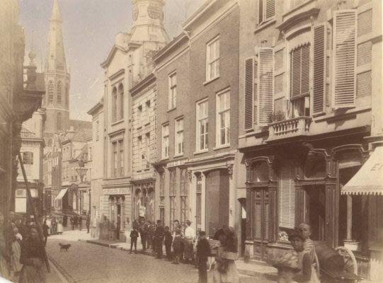 """Gezien vanuit de hoek met de Zeigelbaan, in de richting van de Broerstraat, links de toren van de St. Dominicuskerk ; in het midden boven het klokkentorentje van Sigarenmagazijn """"Noviomagum"""" 1890-1895"""