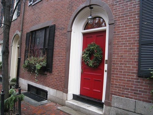 Red Door On Brick House With Black Shutters