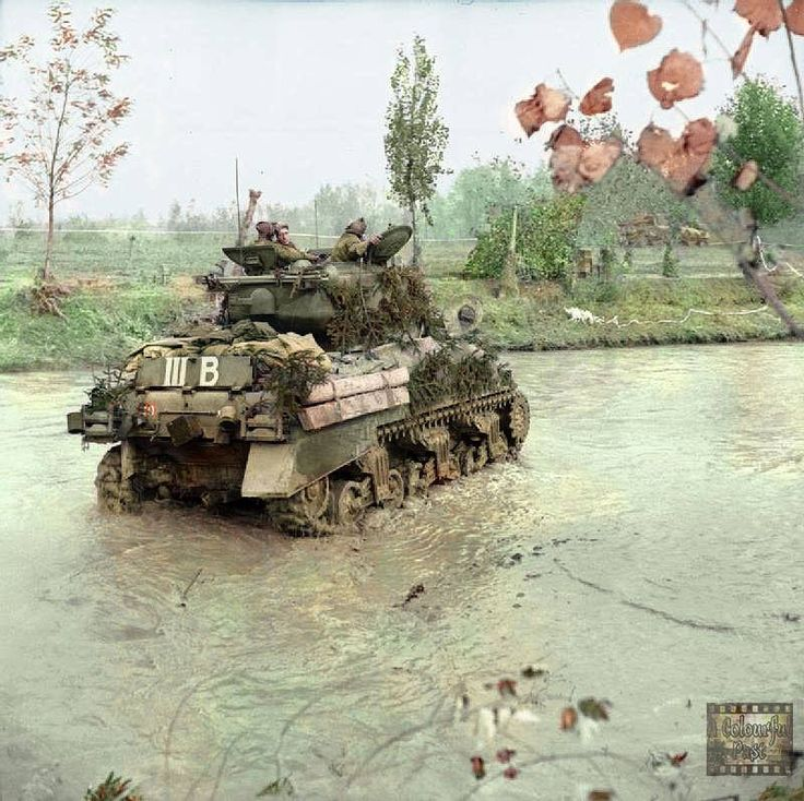 A Sherman IIA tank of 'The Queen's Bays' (2nd Dragoon Guards), 2nd Armoured Brigade, 1st Armoured Division crossing the River Rabbi at San Martino in Strada, Italy. November 9 1944.  On the rear hull, behind the baggage and camouflage, the white '40' on a red square of the senior regiment. The system of Roman numerals and letters can also be seen on the tanks of the other regiments of this brigade.