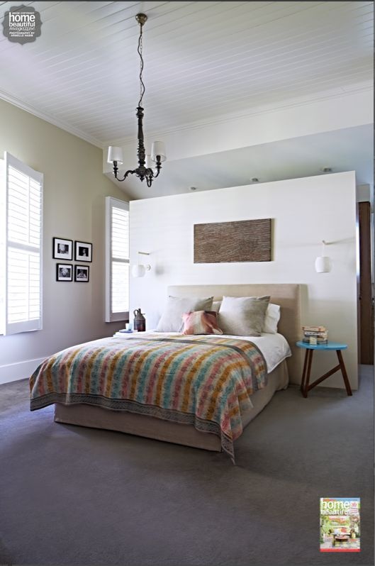 A partition wall in the bedroom conceals the walk-in robe in an understated and natural way