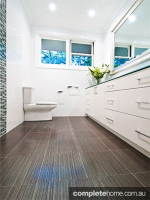 Keep your bathroom designs unique with a dark tiled floor and contrasting walls.