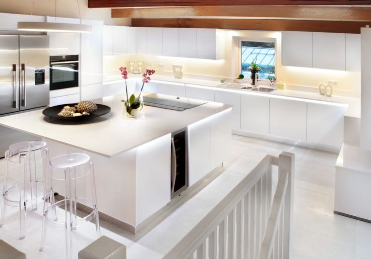 This bright, handleless kitchen has been achieved with the Vitus range in High-gloss White, complemented by a white quartz worktop.