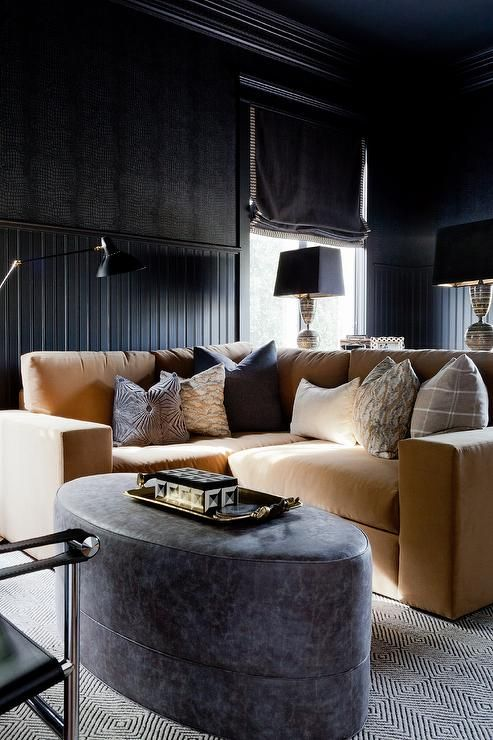 Dramatic black beadboard walls frame a window dressed in a black roman shade in this chic den boasting a camel colored velvet sectional positioned on a white and black diamond patterned rug facing a black oval ottoman.