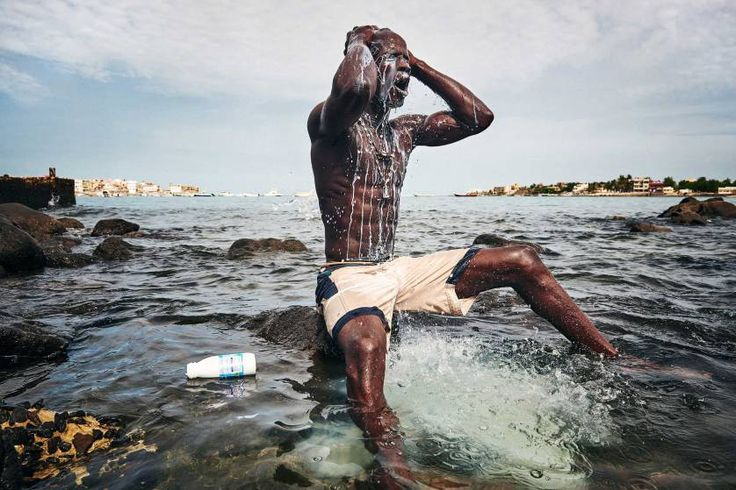 Sports, 2nd prize stories. Wrestlers performing rituals in Senegal. These tournaments resemble a festival including dance performances, music, and wrestling shows. In this photograph, Kherou, a young wrestling champion, performs a ritual in the water of the sea while pouring milk over his body in order to obtain the reinforcement of a ghost who lives in the stones at the shore. Dakar, Sierra Leone, Aug. 11, 2015.