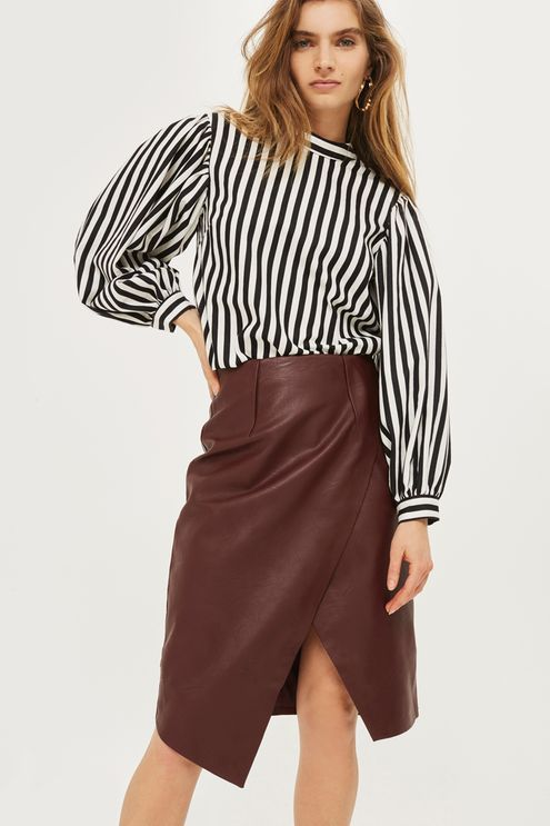 This oxblood coloured PU midi pencil skirt is vintage-inspired and defines sophisticated edge. Show off the wrap over detailing by tucking in a statement striped blouse with balloon sleeves.