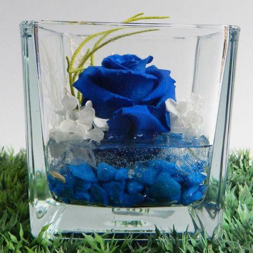 Bellissima composizione con Rosa Blu stabilizzata profumata, disponibile nella misura grande e piccola, racchiusa dentro un raffinato cubo in vetro e adagiata su gel effetto acqua con fondo pieno, fiori e rametti, completa di box regalo in pvc e di certificato di garanzia. Le rose stabilizzate sono rose che non appassiscono mai, mantengono la loro bellezza e il loro inebriante profumo inalterati nel tempo. In promozione su www.mobiliastore.it da e 18,50
