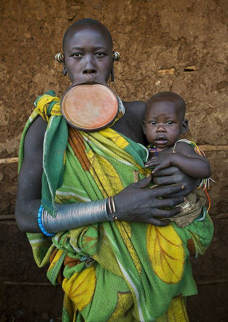Mother and baby with lip plate, Kibish, Omo Valley, Ethiopia    Piercing and lip plates are a strong part of the Suri culture. These traditional adornments are worn by almost all the adult Suri women.