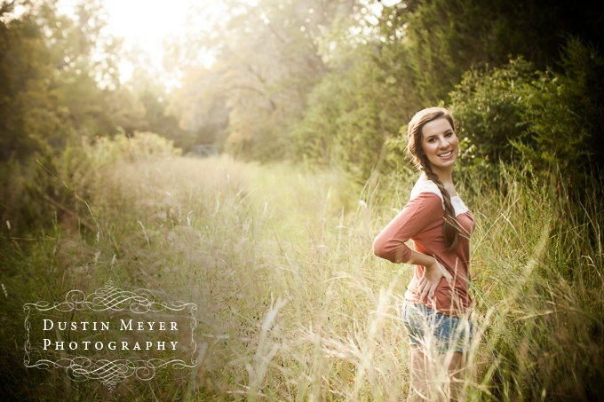 A brunette teen female with a braid in her hair poses in a tall grass field for her senior portraits in Austin, TX.