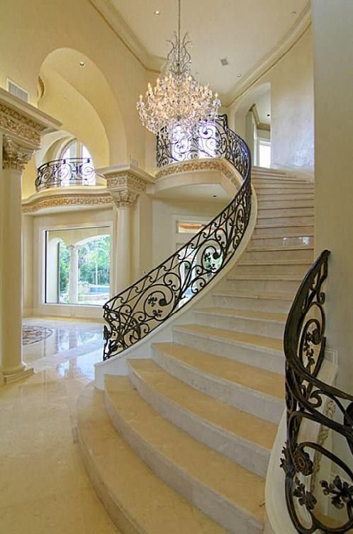 Love the flowing curve of the beautiful stair case and the many other outstanding details going on in this foyer.