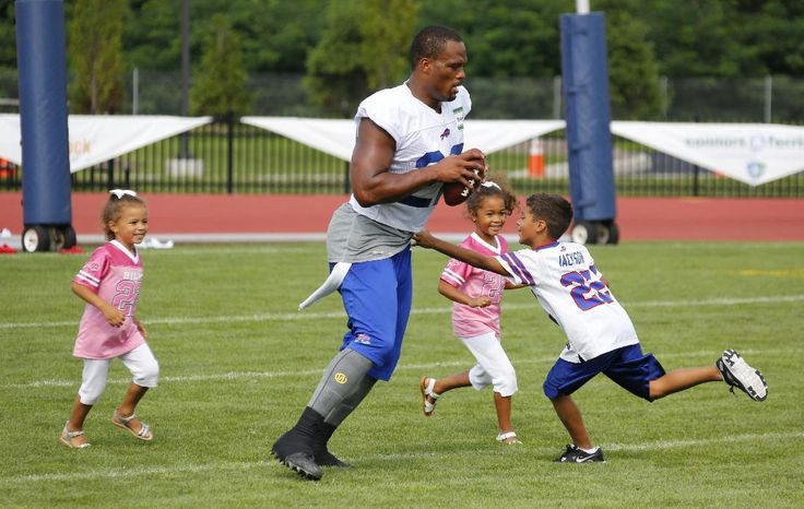 NFL players share tender moments with their kids at training camp - Buffalo Bills running back Fred Jackson (22) plays with his children following a practice at their NFL football training camp in Pittsford, N.Y., Monday, July 21, 2014. With him are daughters Jaeden and Kaelen and son, Braeden (L-R). (AP Photo/Bill Wippert)
