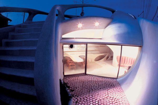 """DER UTERUS VON TOKIO - Wie eine  organische Skulptur windet sich  das zweistöckige Wohnhaus um  einen ruhigen Innenhof. Die  Architekten Ushida Findlay bauten das """"Truss Wall House"""" (1992/93) auf einem winzigen Grundstück in einer  Vorstadt Tokios.  Die Bewohner  leben nach innen, die Betonschale schirmt den Lärm der Straße ab"""