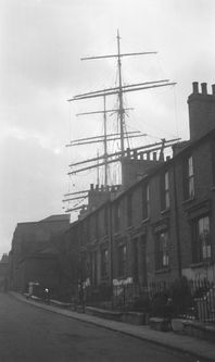Millwall Docks:  The masts and yards of the barque 'Killoran' tower over the houses in Ferry Road, Isle of Dogs on 24th November, 1928