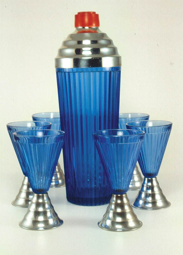 A blue ribbed Deco cocktail shaker with metal top, red knob, and matching glasses, unmarked