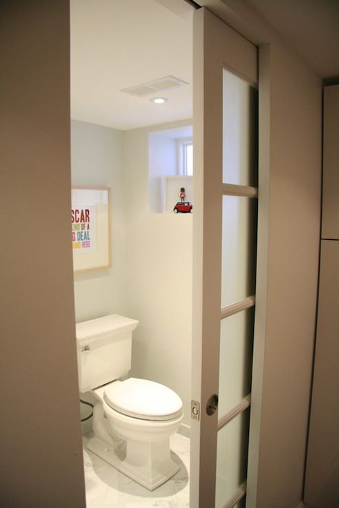 Fantastic basement bathroom with frosted glass pocket door, light gray walls paint color, Kohler memoirs Toilet and Penny Paper Art Print.
