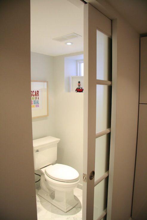 Gain de place, la porte à galandage dévoile des toilettes décorés simplement avec un grand cadre.