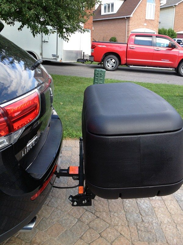 Swinging enclosed cargo carrier for trailer hitch