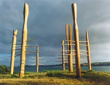 Phil Dadson: Conference of Drums consists of 7 carved slit-drum poles, each with tuned wooden and steel tynes projecting from the outside edges of the centrally located slit-drums, which double as resonator / amplifiers. A set of long wires span the edges of the 7 slit-drum amplifiers, to be played as part of the ensemble. Aeolian wind tones are also produced by breezes through the vertically strung wires and by edge-tone activation of the slit drum cavities.