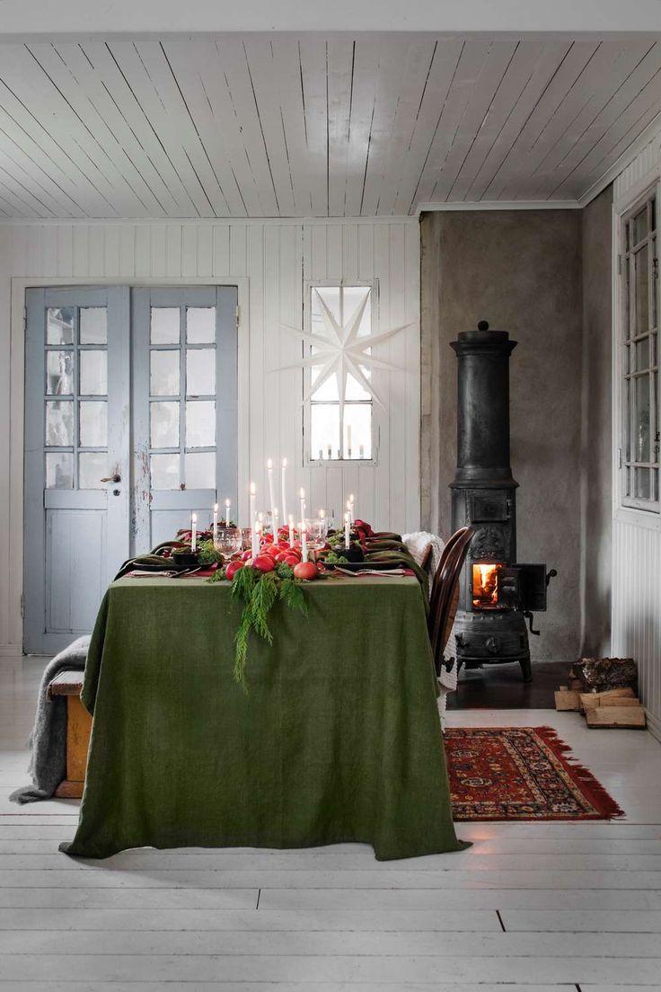 INRED FÖR EN STÄMNINGSFULL JUL | En girlang av tujakvistar, grönkål och röda vinteräpplen med stearinljus blir en magnifik bordsdekoration i all sin enkelhet. En mörkt grön duk blir en lugn bas, 1095 kr, Fritsla tyglager. Pläd till vänster, 599 kr, Svanefors. Pläden över stolen, 799 kr, www.tellmemore.nu. Julstjärna, 199 kr, Coop. Matta, loppis.