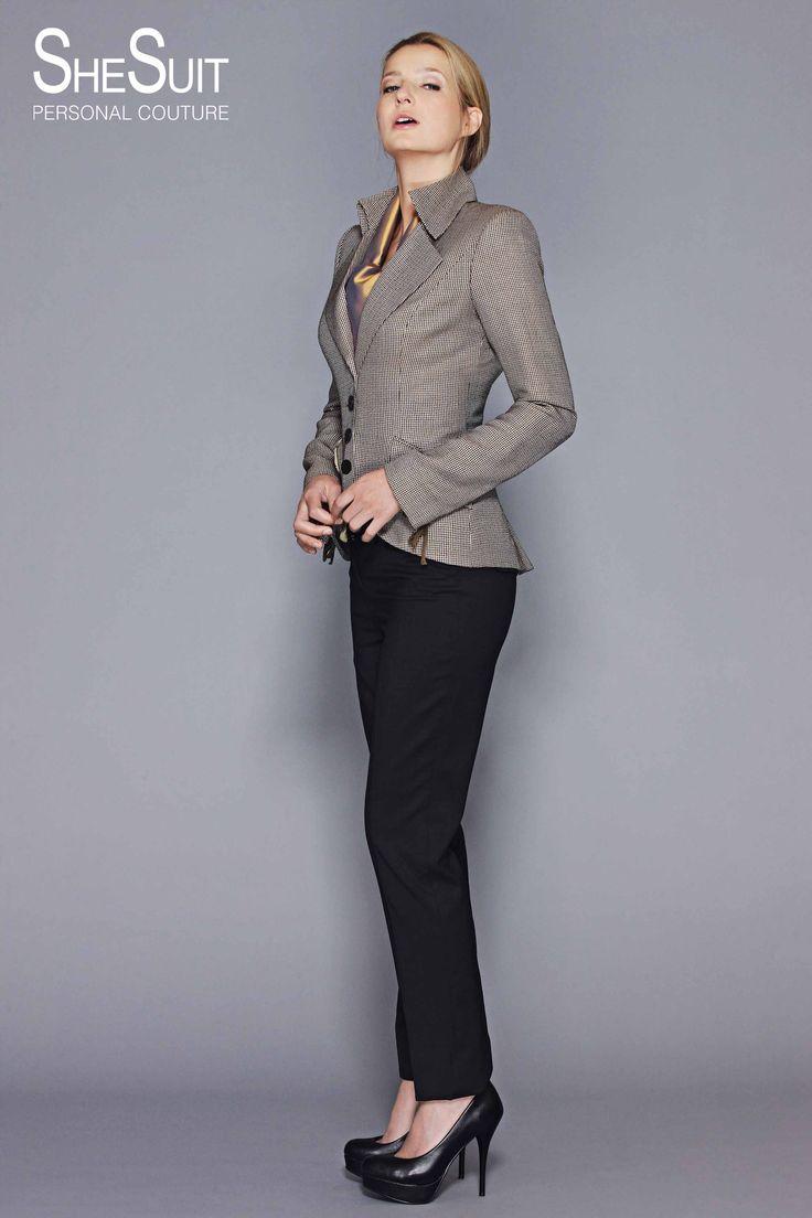 Model Judy. Klassiek sportief wolzijden jasje. Het jasje heeft de bekende SheSuit Napoleonkraag en  is uitgevoerd in een beige bruin wolzijde mengweving. Verder heeft het jasje opvallende rijgsluiting details op de achterzijde en de mouwen.