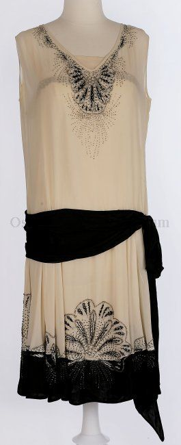 1920s white silk crepe sleeveless dress with drop waist with a slightly flared skirt and a black silk crepe bottom hem, above hem on white crepe is black embroidery and silver and black beads; around V-neck has more of the embroidery and bead decoration, sleeveless with drop skirt, black crepe sash tied in a bow on the right side; large black bow, black embroidery and silver and black beading. Attached white silk crepe underslip has gold lace across the bust line.