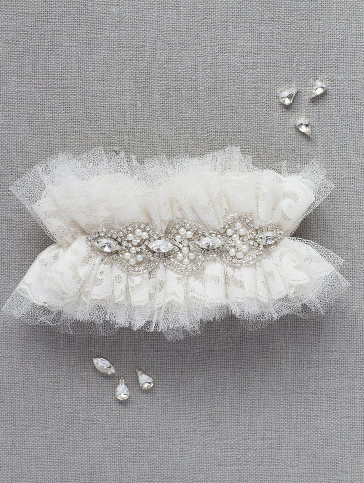 TULLE LACE CRYSTAL PEARL  The Tulle Lace Crystal Pearl garter has layers of Ivory lace and silk tulle adorned with shimmering Swarovski crystals and Ivory pearls.  $250.00   www.emilyriggsbridal.com/