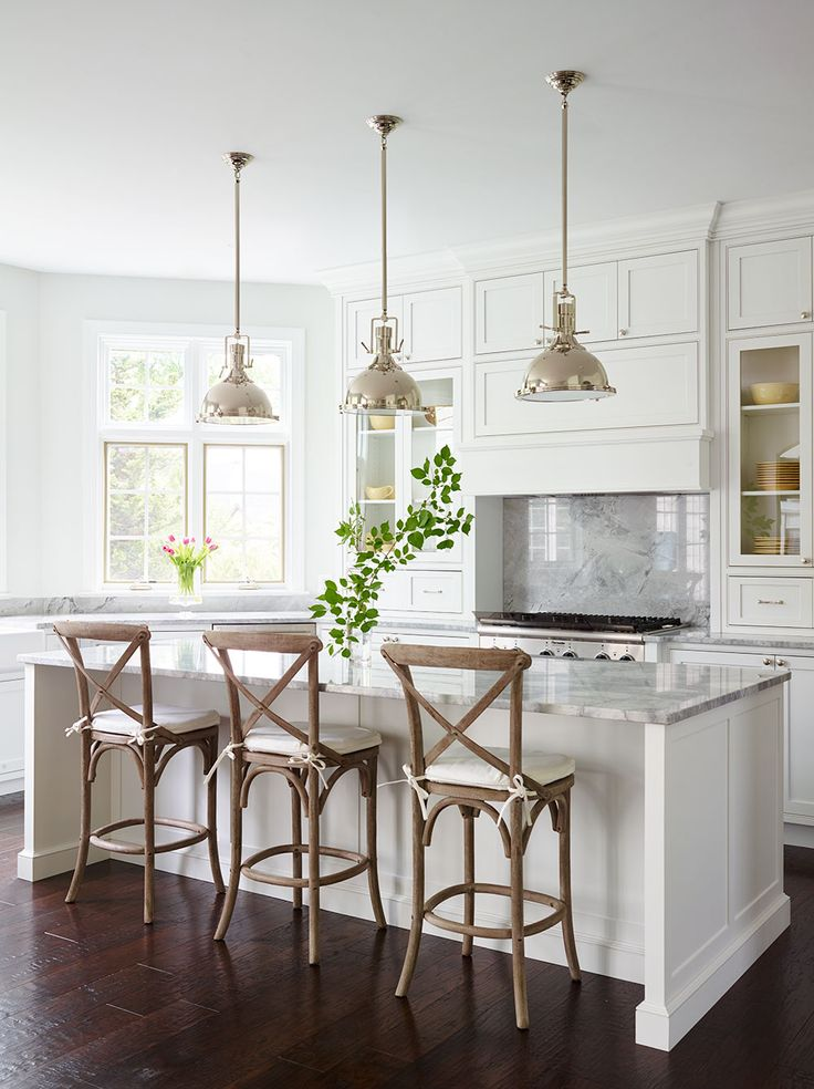 Bright White Custom Kitchen Designed by SHOPHOUSE. Floor to ceiling cabinets, with large island. Quartzite countertops, crown molding and hutch resting on counter. Full slab Backsplash, inset doors and polished nickel lights and hardware. Restoration hardware counterstools and light fixtures