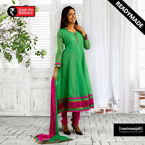 The candy green anarkali kurti in super net moonga checks has a simple neck line with golden string piping and golden buttons.The hemline has an overlay of woven lace and 2 coloured tapings around it. The bottom in rani pink and has a 2 toned chiffon dupatta.  For more details and online shopping visit www.vastraanjali.com