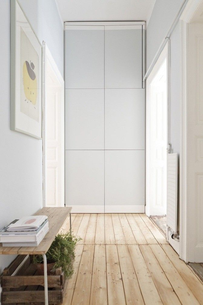 Built-in storage in entry hall of White bedroom with pine floors  in Wiesbaden Apartment by Studio Oink | Remodelista