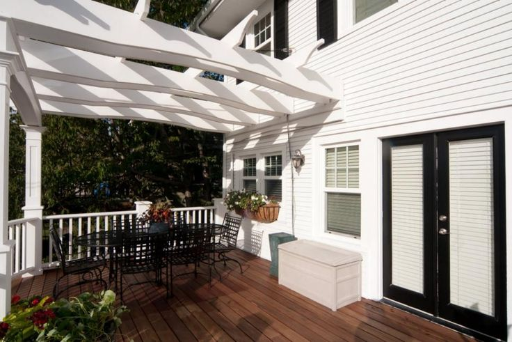 This traditional craftsman home boasts a spacious deck area with medium brown wood planks and a curved white railing. A white pergola is positioned over a black metal dining set, providing a comfortable spot for enjoying the outdoors.