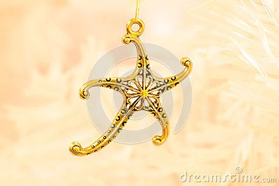 A close up  of a gold coloured starfish  pendant on the branch a white Christmas tree.