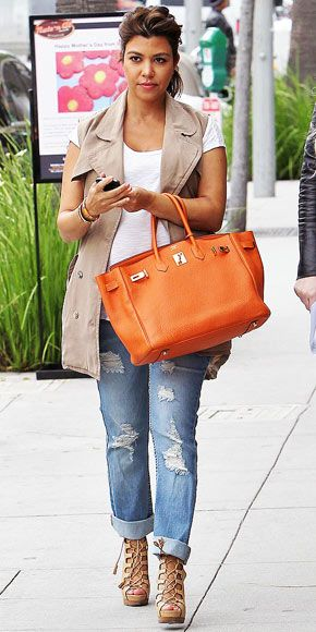 kourtney kardashian in a cargo vest, distressted jeans and a beautiful coral birkin bag for some pop!