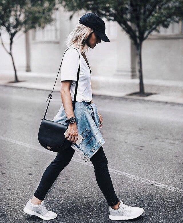 Black vs leggings, white tee, baseball cap. Black bag. Denim jacket tied around waist. Sneakers