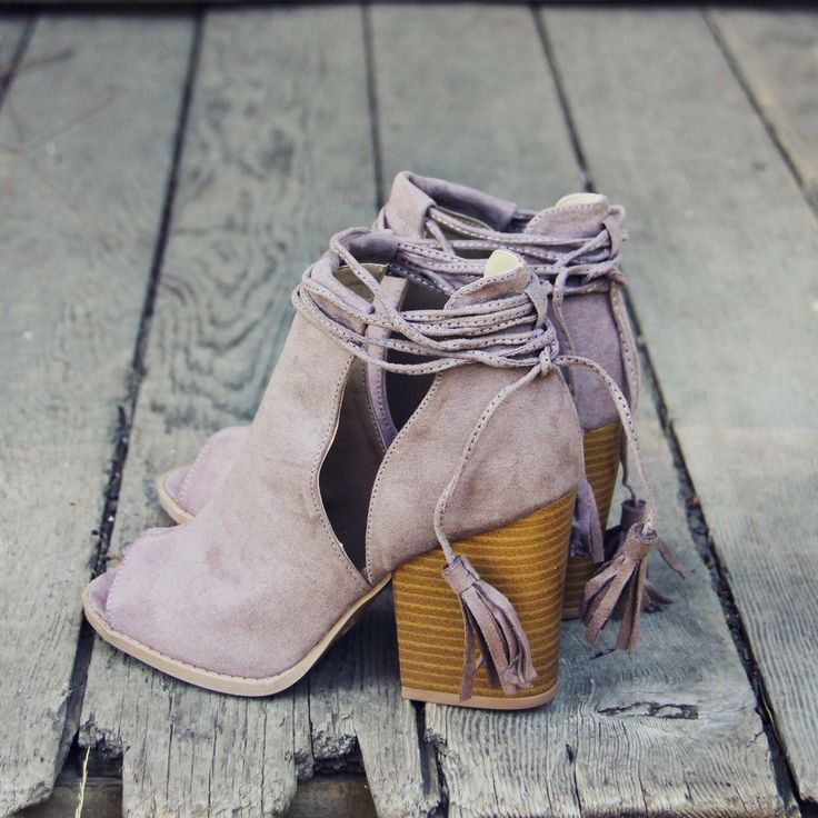 Gorgeous tassel details adorn these darling booties. Designed with a stacked heel, peep-toe design, and wrapped ankle. Soft taupe toned…