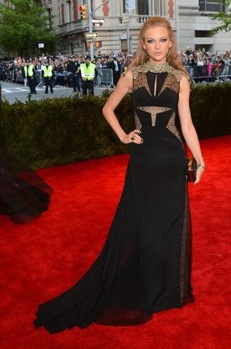 Taylor Swift não fugiu de seus modelos de costume, mas se destacou ao combinar perfeitamente o vestido preto com veludo e recortes, cabelo com mechas pink e maquiagem mais pesada.