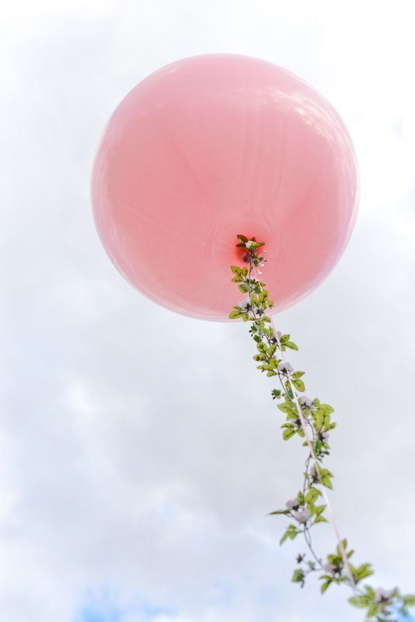 flying pink balloon with green leaves
