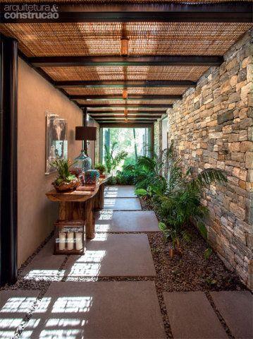 Quem entra na morada ou passa de um bloco ao outro atravessa este corredor, com teto de vidro e palha de dendê (Fibra Nativa), solução que barra a chuva e deixa passar uma suave luz filtrada. No piso, pré-moldados de concreto no tom cinza-escuro (ref. 2932), da Stone. Projeto de Gui Mattos.