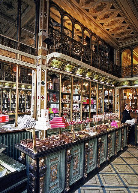 Fabulous sweet shop in traditional vintage style. I love the play of horizontal and vertical lines on the cabinets and the wall that create a harmony while the diagonal lines on the floor add interest. The interior feels inviting and looks organized.
