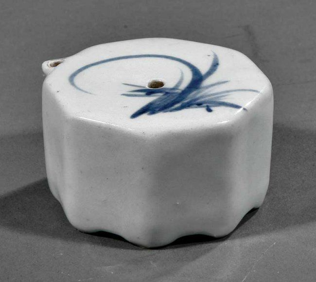 A Korean Blue and White Porcelain Water Dropper, probably late Joseon Dynasty (1392-1896), octagonal body with scroll spout raised on eight incurvate feet, freely decorated to the top side with a cymbidium orchid and foliage, height 1 1/2 in., width 2 3/4 in
