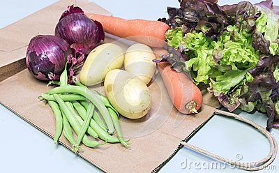 Garden fresh carrots, green beans, potatoes, red onions and variegated lettuce displayed on a brown paper shopping bag.