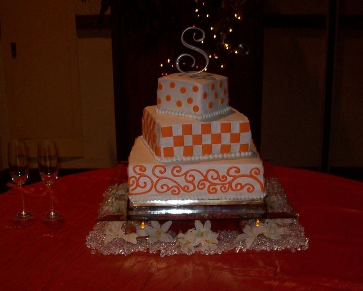 This wedding cake was done for a TN. Vols Football Team wedding theme. The Cake was done in the Traditional White cake with my White wondercream buttercream icing and fondant squares and circles, handpiped buttercream scrolls.