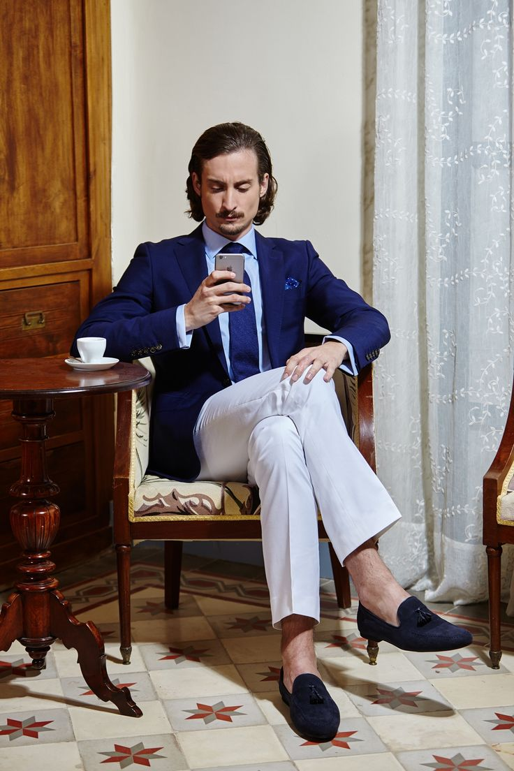 Men's casual blue suit jacket with contrast white tailored trousers and a crisp light blue tailored shirt.