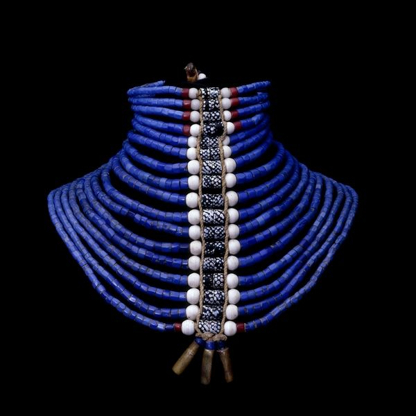 This particular neck ornament, with its central band of patterned Venetian beads and brass cartridge cases, would be worn by a Dinka man at or shortly before his wedding to show his eligibility and the wealth of his family in cattle. The beads themselves would either have been traded across the savannah from West Africa or brought inland from the East African coast.