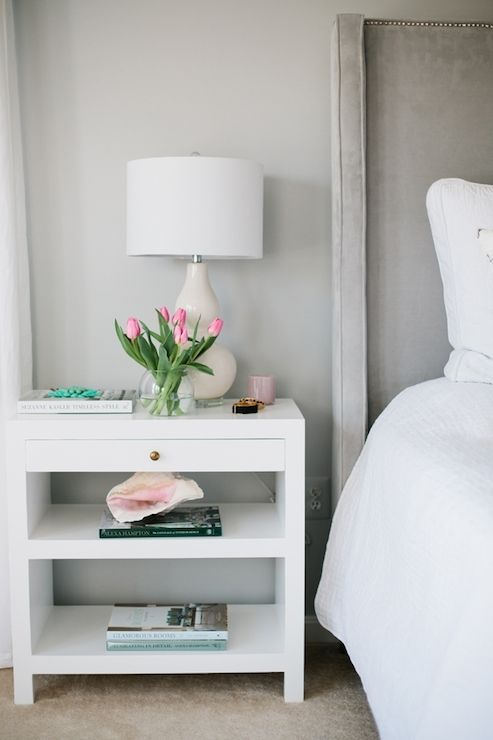 Simply stunning bedroom features light gray walls as a backdrop for a gray velvet headboard with silver nailhead trim dressed in soft white bedding situated next to white lacquer nightstand with brass hardware topped with cream double gourd lamp.