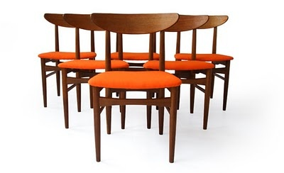 More retro dining chair fun! I like the warm dark wood combined with the bright orange seats.