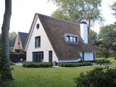 Moderne witte villa met rieten dak en strak zinken dakkapel
