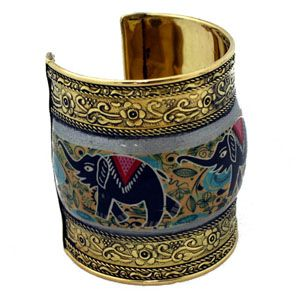 Wrap your wrist in exotic culture with this painted brass cuff. Elephants have trunk up adding a bit of good luck too!