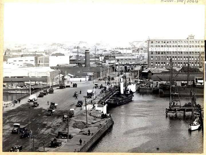 Spencer Street Bridge with motor vehicles and pedestrians viewed from north side of Yarra River,tug boat up against the edge of the bridge, Robur Tea warehouse on right.Also in background - Eckersley's Soda Fountain Works 1929.
